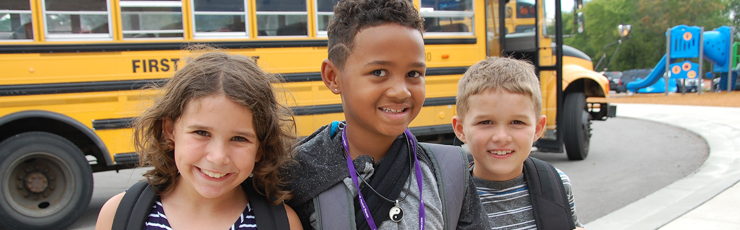 Students in front of the school bus on the first day of school.